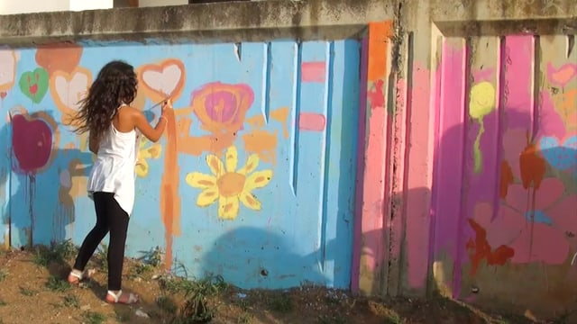 Ein Mädchen bemalt eine Mauer.