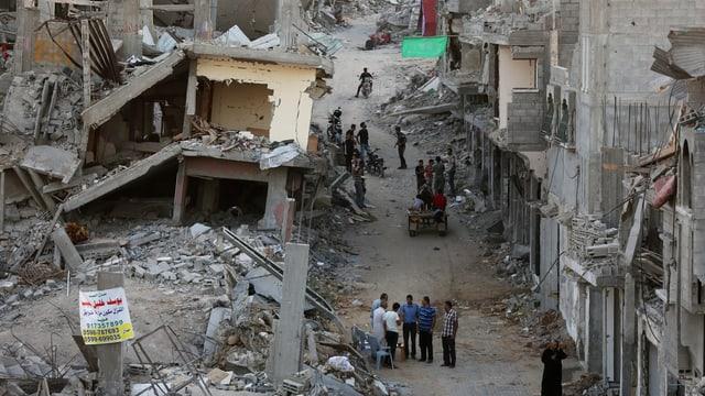 Zerbombtes Quartier in Gaza, einige Menschen stehen zwischen den zerstörten Gebäuden auf der Strasse.
