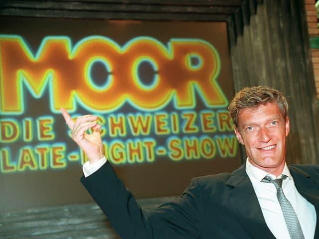 Ein Mann in Anzug und Krawatte sitzt mit erhobener Hand vor einer grossen Leinwand, auf der «Moor» steht.