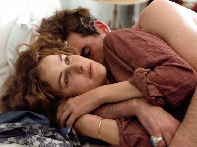 Eine Frau und ein Mann liegen umschlungen in einem Bett