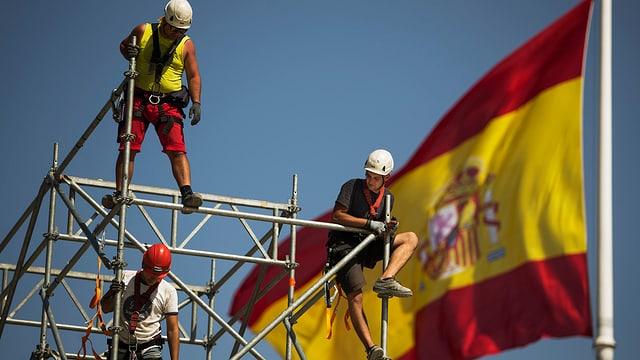 Bauarbeiter errichten ein Gerüst vor einer spanischen Flagge.
