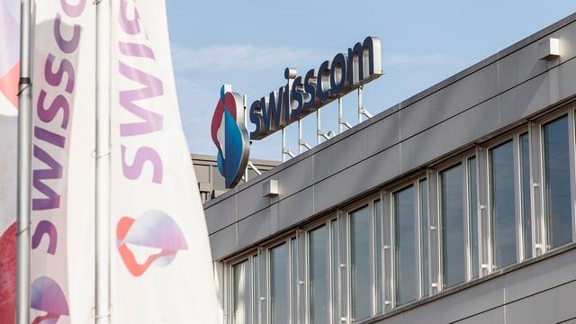Vista sin il bajetg da la Swisscom. Logo da la Swisscom sin il tetg dal bajetg. Davanttiers bandieras cun si il logo.