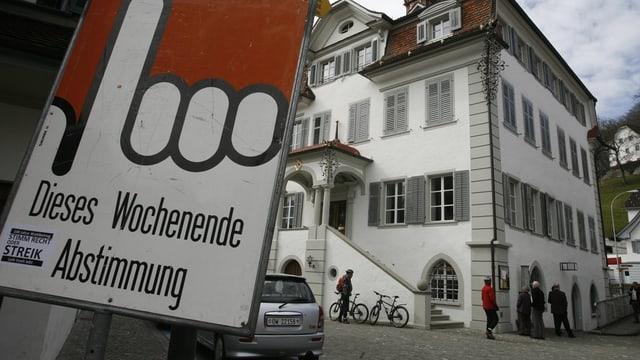 Ein Plakat steht vor einem weissen Gebäude