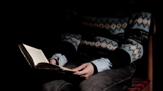 Jemand liest ein Buch. Der Kopf ist verdeckt.