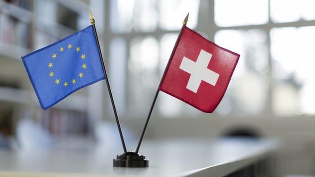 Kleine Fahnen von der EU und der Schweiz auf einem Tisch