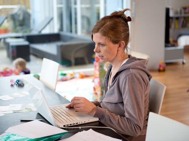 Kerstin Birkeland Ackermann vor ihrem Computer am Familientisch sitzend.