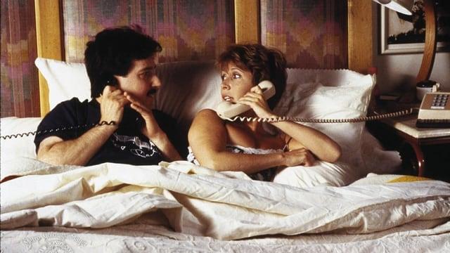 Ein Paar liegt im Bett. Beide haben einen Telefonhörer in der Hand.