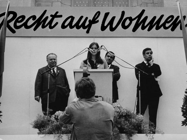 Bühne mit Rednerpult. Claudia Honegger hält eine Rede und ist flankiert von drei Männer.