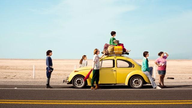 Ein gelbes Auto auf einer einsamen Strasse, rundherum Kinder und zwei Frauen.