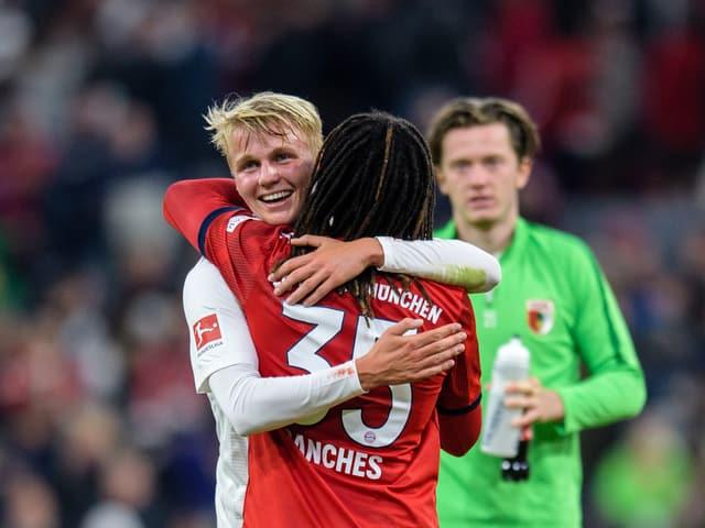 Felix Götze strahlt und wird von Renato Sanchez umarmt.