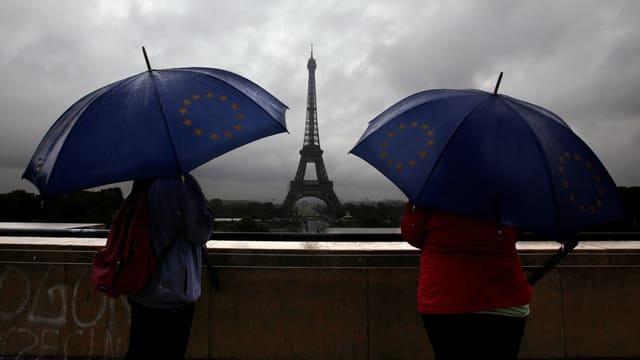 Zwei Personen unter blauen Regenschirmen schauen in Richtung des Eiffelturms.