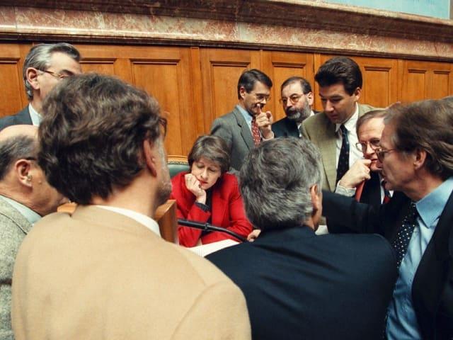 Frau sitzt im Ratssaal umringt von Parlamentarieren.