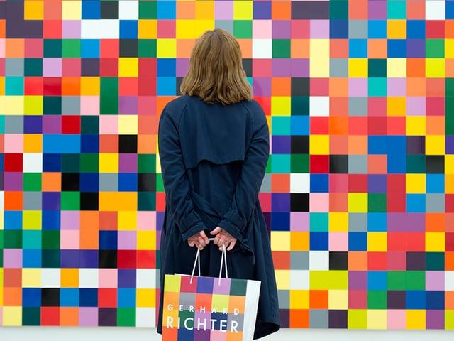 Eine Frau von hinten, die vor einem Bild mit zahlreichen kleinen bunten Quadraten steht.