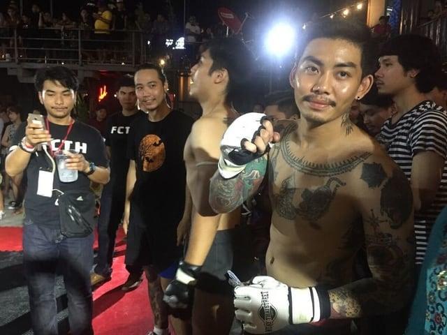 Ein junger Mann mit weissen Kampfhandschuhen und voll tätowiertem Oberkörper posiert vor der Kamera und neben ihm sein nächster Gegner Em.