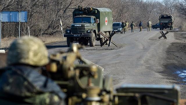 Lastwagen und ein Soldat mit Waffe im Anschlag
