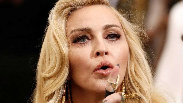 Madonna blickt mit erhobenem Zeigefinger in die Kamera