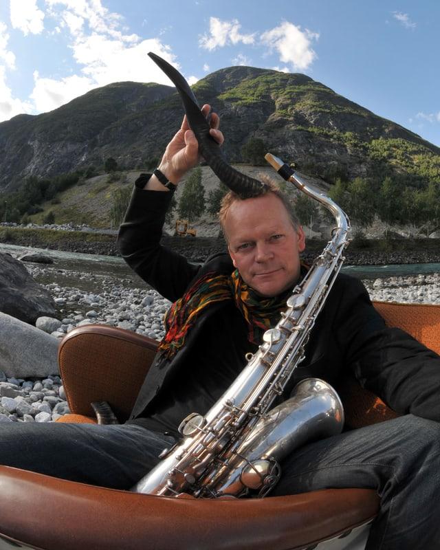 Ein Mann mit Horn und Saxophon sitzt auf einer Couch von Steinen umgeben.