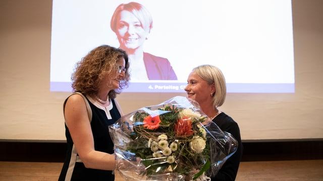 Eine Frau überreicht einer anderen Frau Blumen.