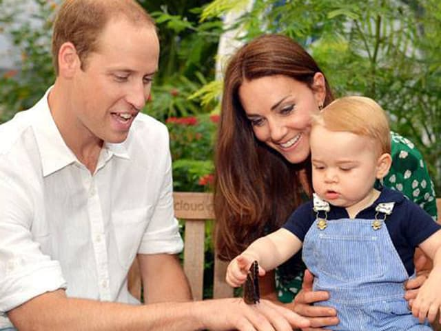 Prinz George auf der Schoss von Kate sitzend zeigt auf einen Schmetterling der auf Williams Hand platzgenommen hat.
