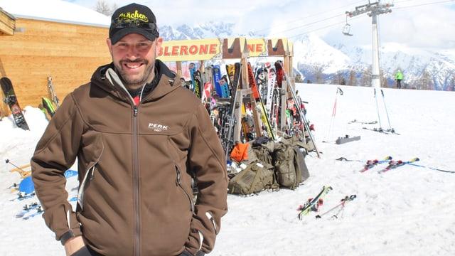 Ein Mann steht vor einem Skiständer und lacht in die Kamera.
