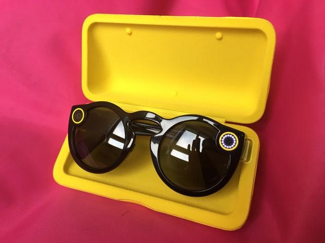 Snapchat Spectacles in ihrer gelben Schachtel.