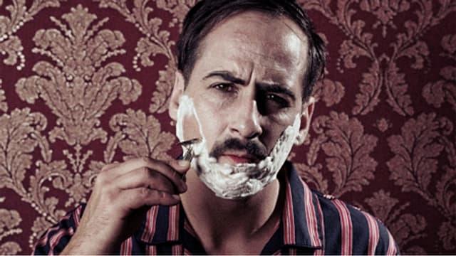 Zu sehen ist King Pepe vor einer altmodisch anmutenden Tapete. Er trägt ein Pijama und ist dabei, sich zu rasieren.