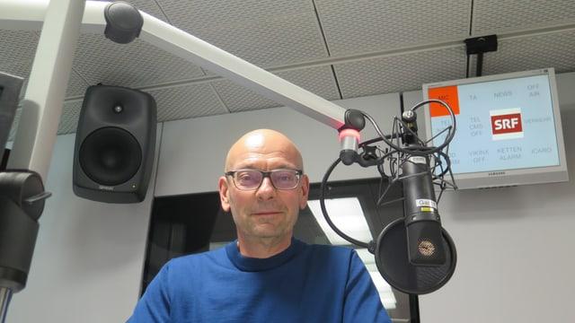 Ein Mann mit Glatze und Brille hinter einem Mikrofon.
