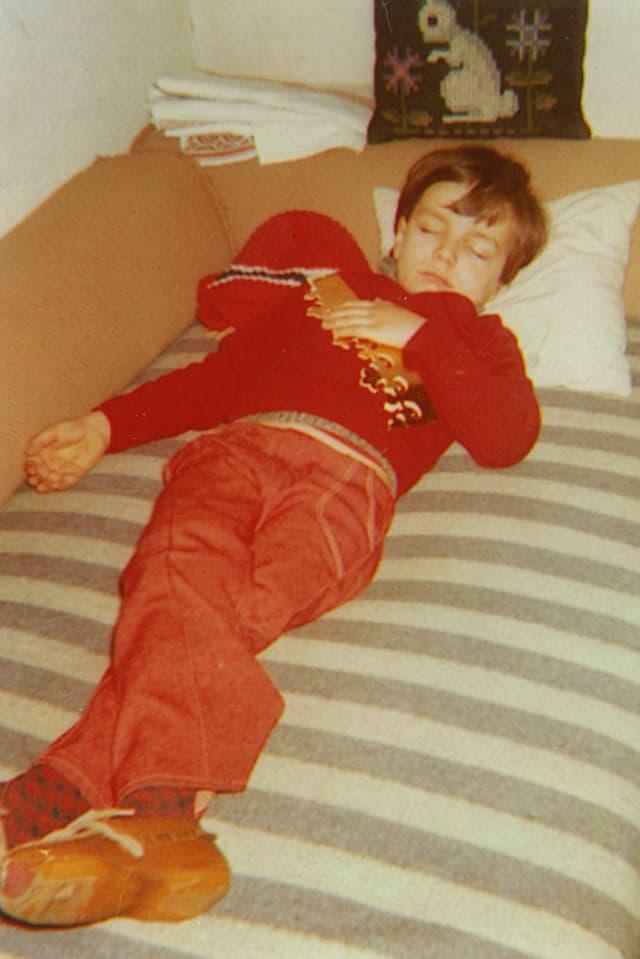 Kleiner Junge liegt mit abgelatschten Finken auf Bett.