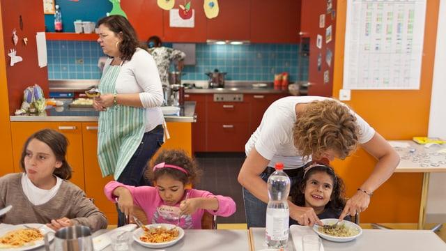 Hortbetreuerinnen servieren den Kinden das Mitagessen