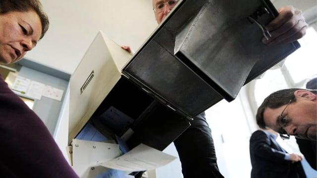 Abstimmungsurne wird geleert unter Beobachtung von Helfern.
