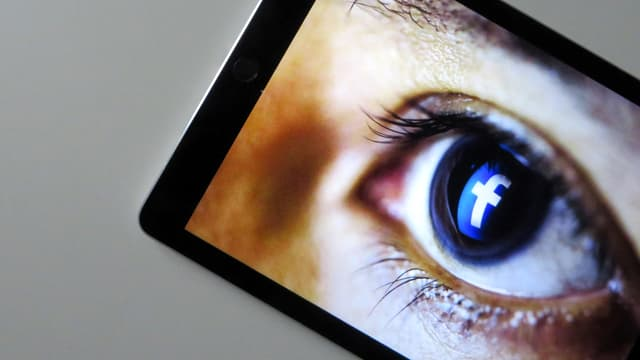 Ein Auge mit Facebook-Zeichen in der Pupille, auf einem Screen.