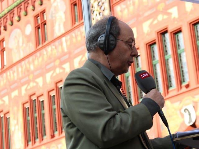 Moderator Peter Bollag mit Mikrofon vor dem Basler Rathaus.