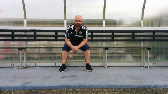 Christian Kühni sitzt auf der Trainerbank des FC Gossau. Er hat ganz kurze Haare und ein blaues Trikot des FC Gossau an.
