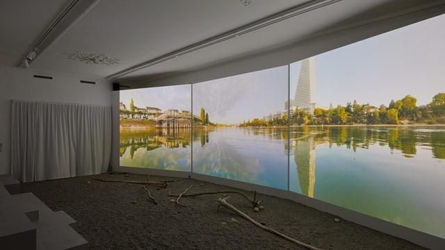 Drei grosse Bildschirme zeigen den Rhein.