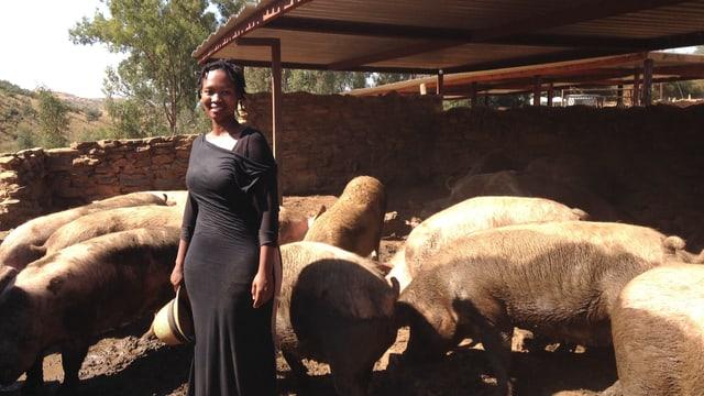 Schwarze Frau. Sie steht in einem Gehege mit Schweinen.