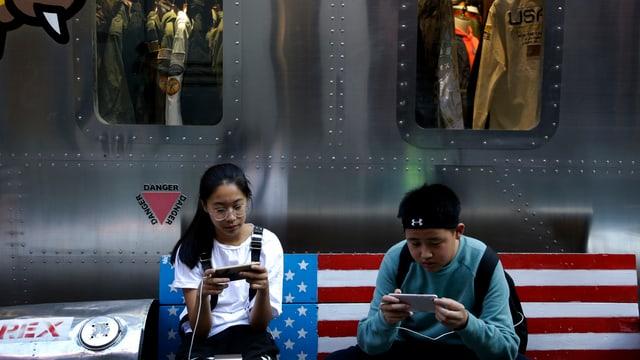 Zwei Jugendliche auf einer Bank im US-Look in einer Pekinger Mall