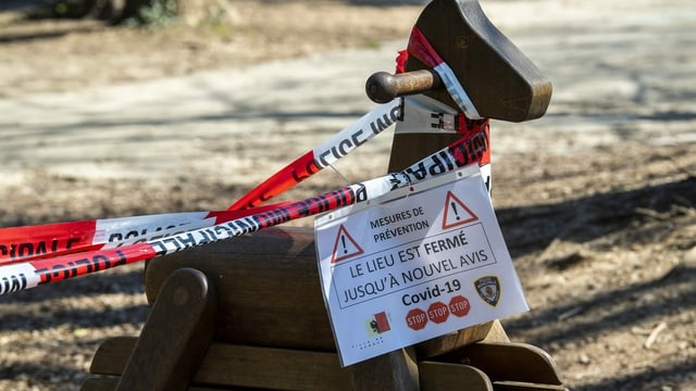 Schaukelpferd auf Spielplatz mit Corona-Hinweisschild