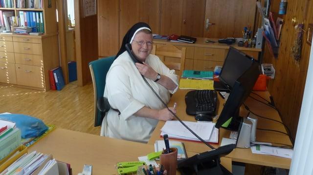 Sora Madlen Büttler e gist vit il telefon en ses biro da la claustra da Glion
