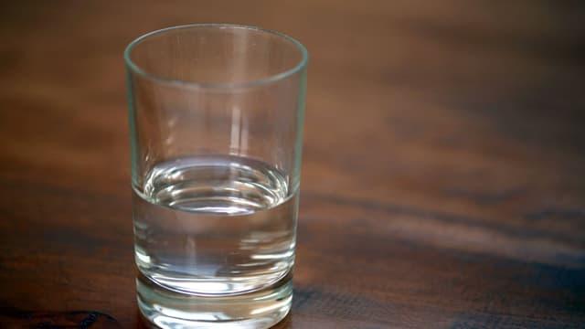 Ein halbvolles Glas steht auf einem Tisch.