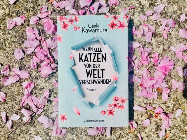 Der Roman «Wenn alle Katzen von der Welt verschwänden» von Genki Kawamura liegt auf Kirschblüten