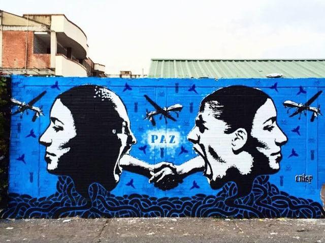 Graffito: Zwei Köpfe, verbunden über Arme, die sich die Hand reichen.