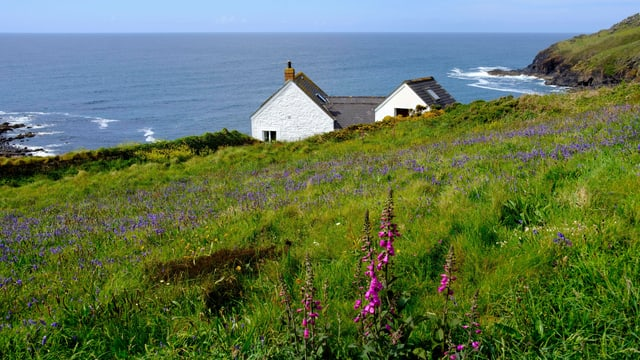 Ein Haus im Grünen, im Hintergrund das Meer.