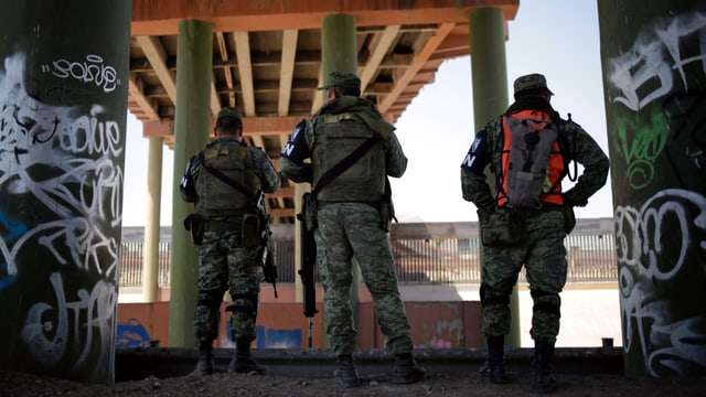 Soldaten stehen unter einer Brücke