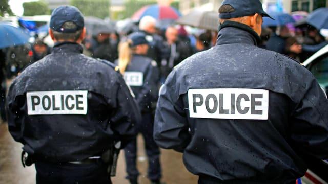 Zwei französische Polizeibeamten von hinten.