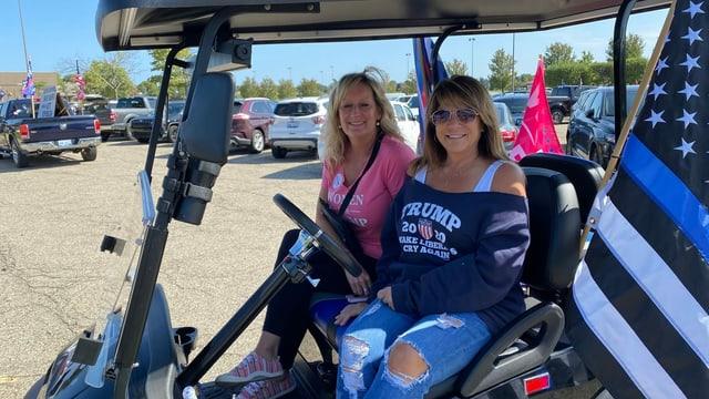 Zwei Frauen in einem Golfwagen.