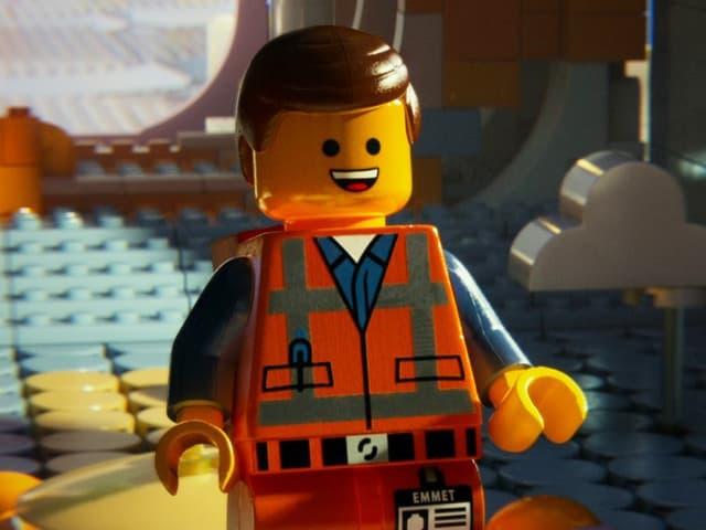 Ein Legomännchen mit scheitelfrisur und orange-farbener Arbeiterkluft.