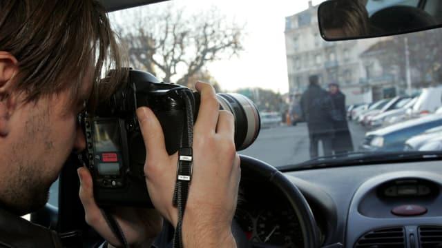 Ein Mann richtet ein Kameraobjektiv auf zwei menschne auf einem Parkplatz.