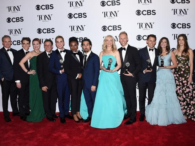 Dreizehn Personen stehen vor einer Fotowand und posieren mit ihrem Preis.