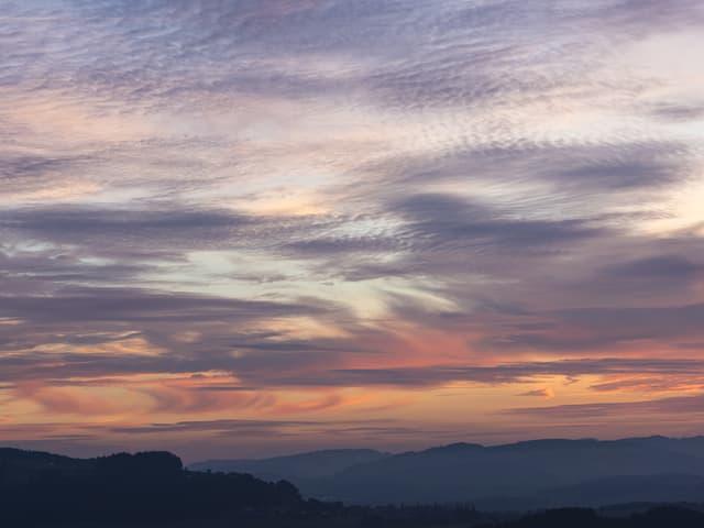 Himmel mit wenigen dünnen Wolken in rosa und lila.