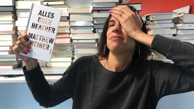 Annette König hält den Roman «Alles über Heather» von Matthew Weiner in der Hand und greift sich mit der andern Hand an den Kopf